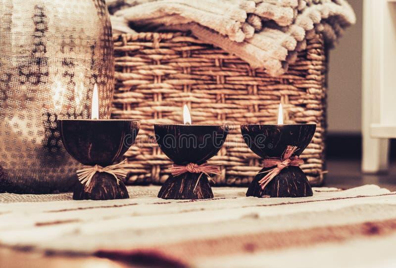 Decorazione interna domestica accogliente, candele brucianti di una su una coperta colorata multi sui precedenti di un contenitor fotografia stock libera da diritti