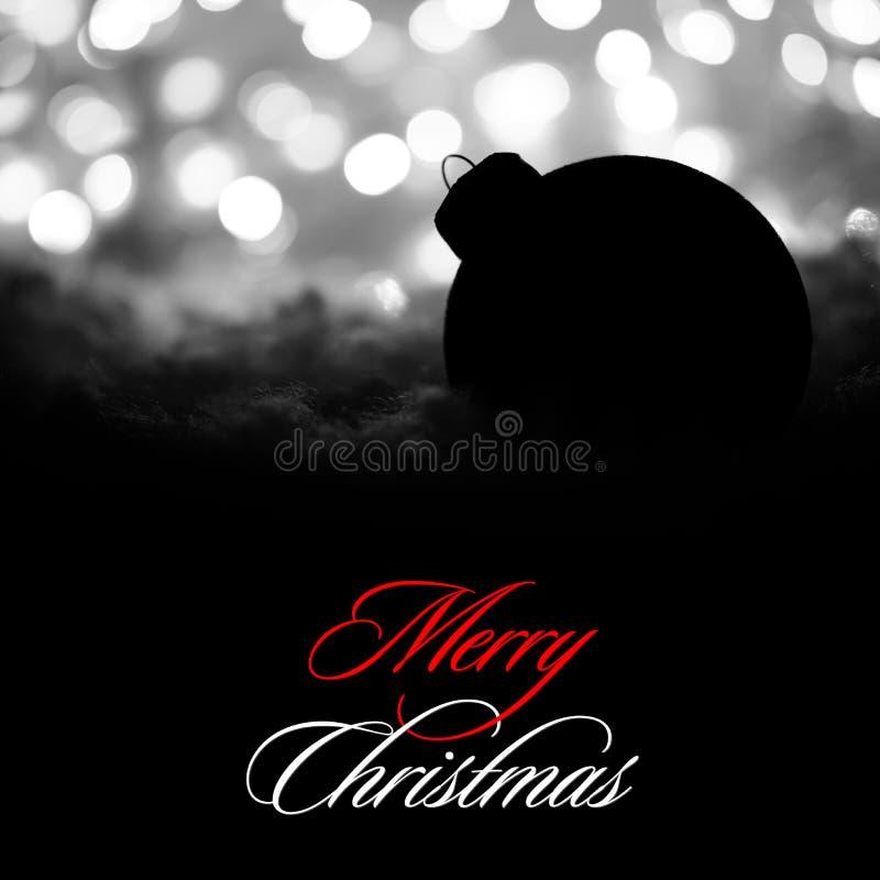 Decorazione misteriosa di Natale con la palla nera nella neve sui precedenti delle luci di festa vaghe bianco Cartolina d'auguri fotografie stock