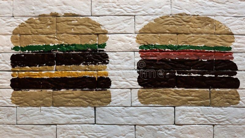 Decorazione per la pubblicità del fast food o del caffè Sul muro di mattoni bianco è un cheeseburger estratto di due hamburger o fotografie stock