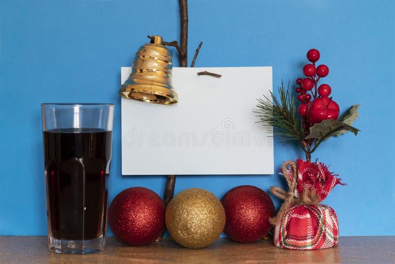 Decorazione per Natale e Capodanno: cartolina di auguri con carta bianca per messaggi, tre palline decorative e vetro pieno fotografia stock