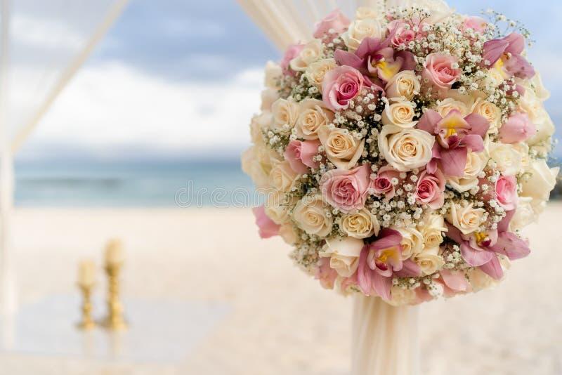Decorazione romantica con i fiori delle nozze di spiaggia sulla spiaggia con il mare nei precedenti immagine stock