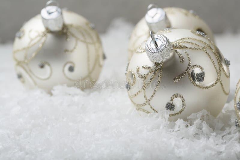 Decorazioni d'argento di Natale su neve immagini stock