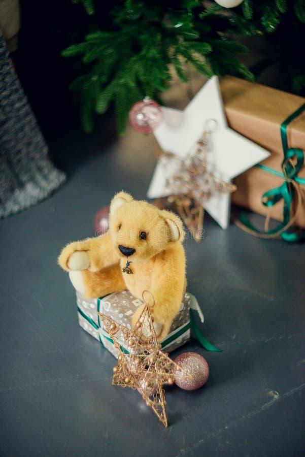 Decorazioni del nuovo anno nei colori blu e beige Giochi l'orso, le lanterne bianche decorative ed i contenitori di regalo sotto  fotografie stock