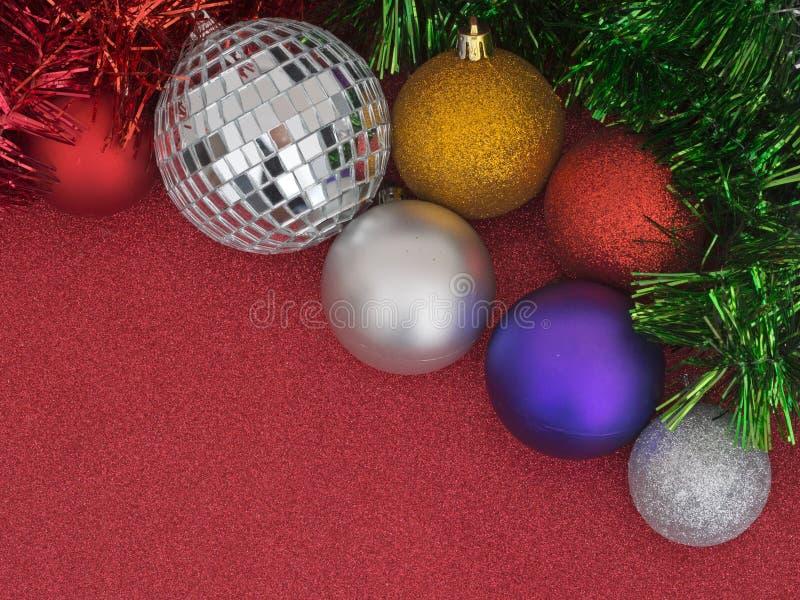 Decorazioni dell'albero di Natale, bagattelle e lamé, su rosso luccicante fotografie stock libere da diritti