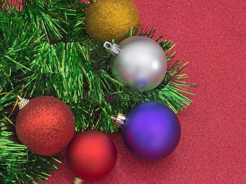 Decorazioni dell'albero di Natale, bagattelle e lamé, su rosso luccicante fotografia stock libera da diritti