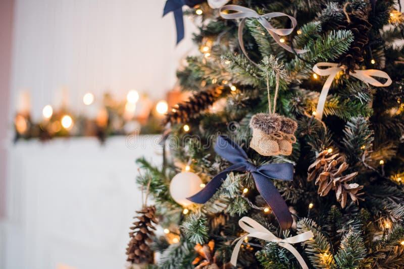 Decorazioni dell'albero di Natale Giochi gli feltro-stivali ed archi e coni tricottati dell'annata sull'albero di cristmas Chiuda fotografia stock