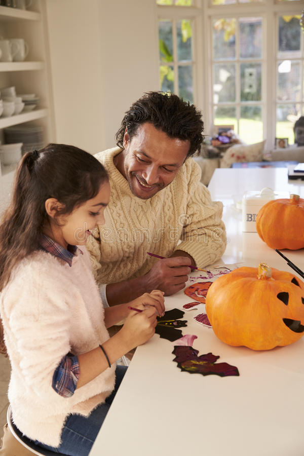 Decorazioni di And Daughter Making Halloween del padre a casa fotografia stock libera da diritti