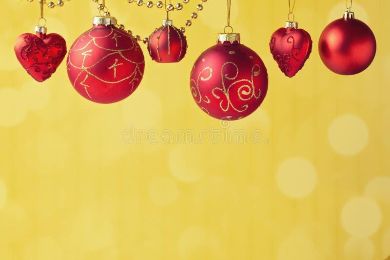 Decorazioni di Natale che appendono sopra il fondo dorato del bokeh con lo spazio della copia fotografia stock