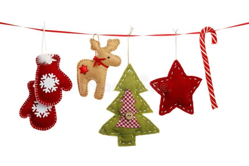 Decorazioni di Natale che appendono su un nastro rosso immagini stock