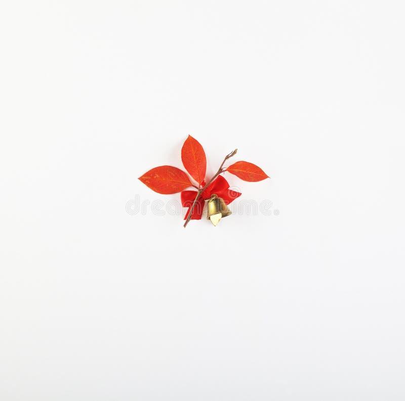 Decorazioni di Natale - foglie, nastro e campana di rosso isolati su fondo bianco fotografia stock libera da diritti