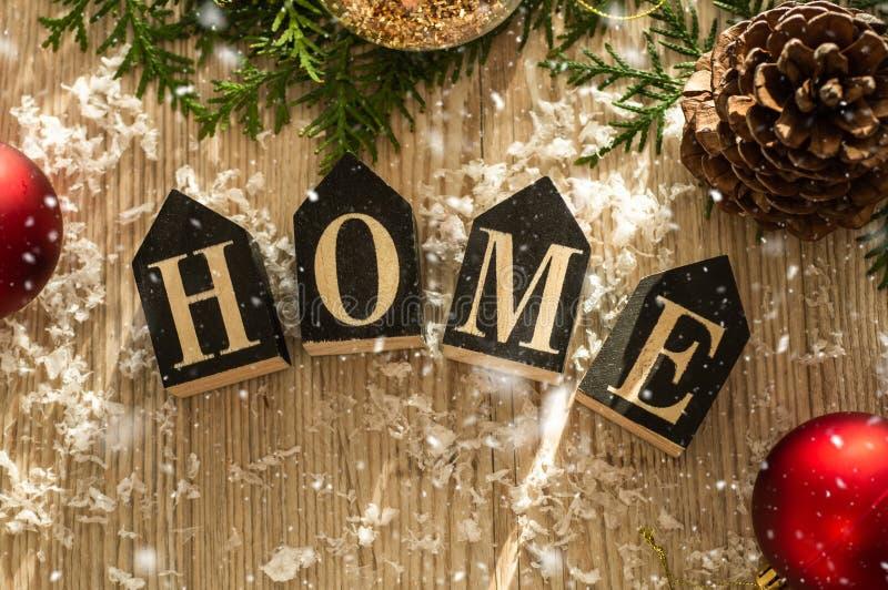 Decorazioni domestiche nei precedenti di legno di una lettera con una casa dell'iscrizione Decorazioni e neve di Natale Camera, c fotografie stock libere da diritti
