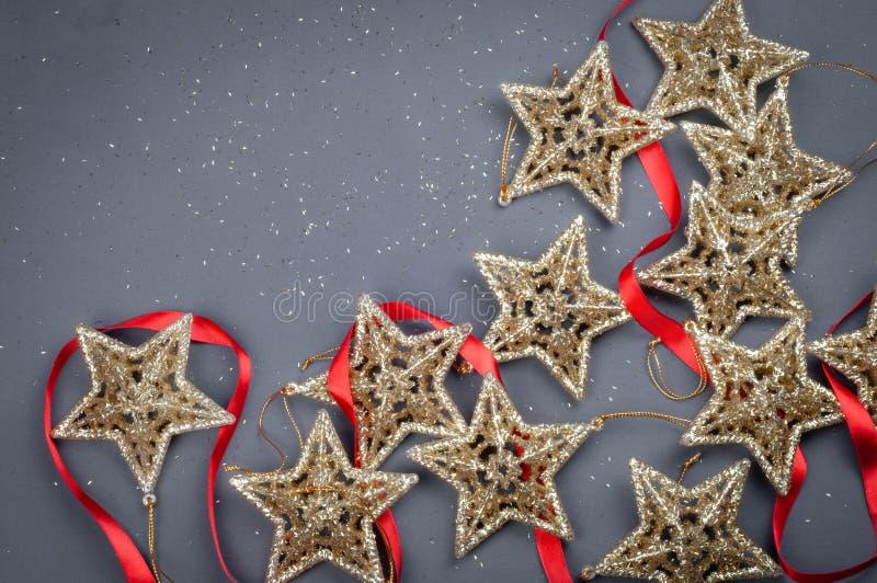 Decorazioni dorate della composizione in Natale delle stelle su un fondo grigio con il nastro rosso fotografia stock