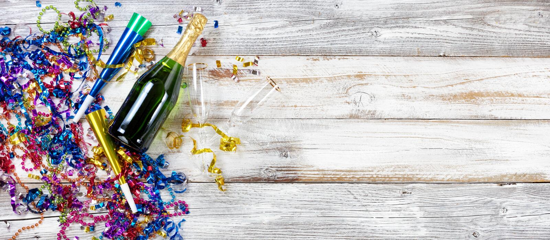 Decorazioni e champagne del partito del nuovo anno su legno bianco rustico immagini stock