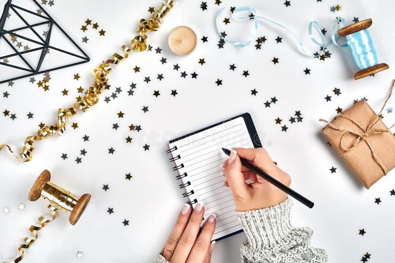 Decorazioni festive, nastri ondulati delicati, coriandoli a forma di stella metallici e taccuino con la lista di obiettivi sulla  immagini stock libere da diritti