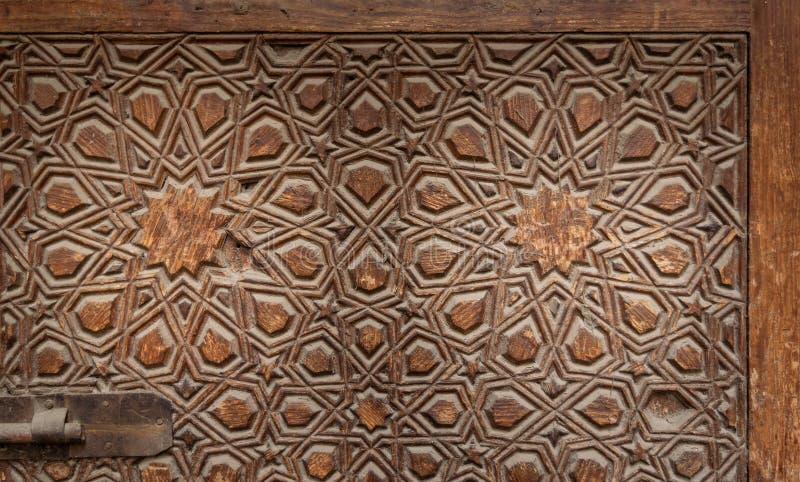 Decorazioni geometriche incise incisive di una foglia di una porta ornata di legno di età immagini stock libere da diritti