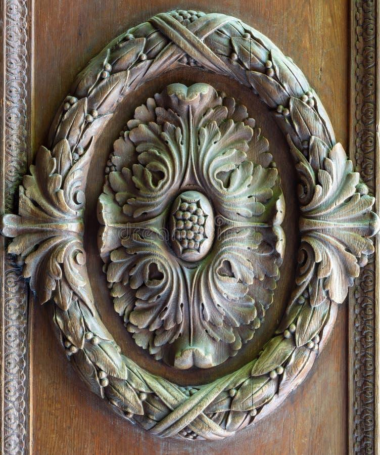 Decorazioni incise floreali di un battente decorato di legno di era reale fotografia stock