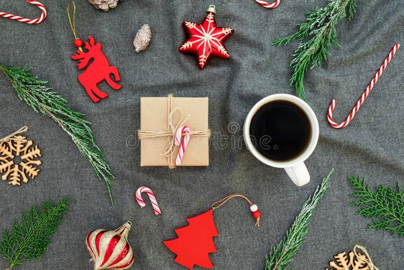 Decorazioni rosse di Natale, rami di albero sempreverdi, tazza di caffè e contenitore di regalo sul plaid grigio Disposizione pia fotografia stock libera da diritti