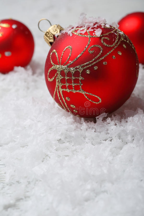 Decorazioni rosse di natale su neve artificiale immagine stock