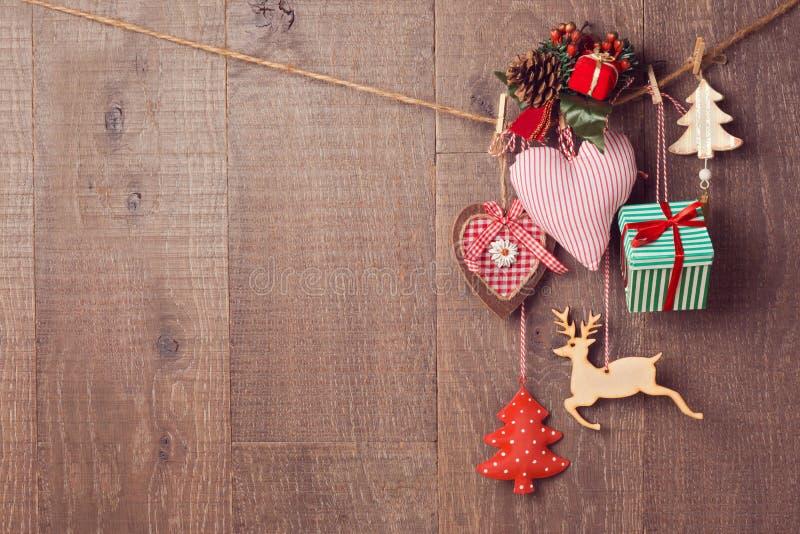 Decorazioni rustiche di Natale che appendono sopra il fondo di legno con lo spazio della copia fotografie stock libere da diritti