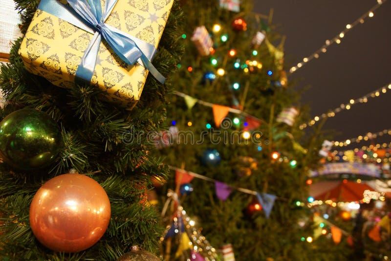 Decorazioni su un albero di abete di Natale, luci di Natale del fondo di un mercato di Natale su un quadrato rosso, fotografia stock