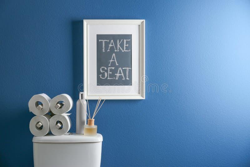 Decorelementen, noodzaak en toiletkom dichtbij blauwe muur Badkamers stock afbeeldingen