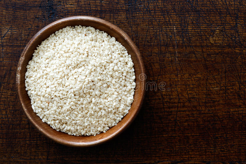 Decorticated sesame seeds in dark wooden bowl isolated on dark b royalty free stock photo