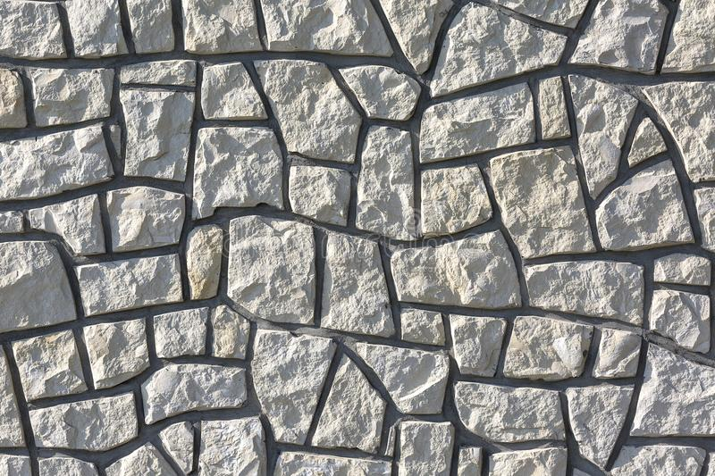 Decotative stone wall from pieces of stone, background.  stock photos