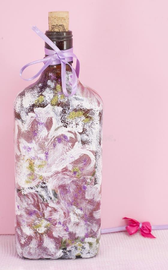 Decoupage adornó el fondo rosado del bottleagainst imágenes de archivo libres de regalías