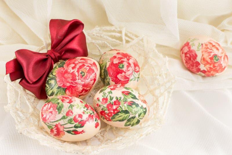 Decoupage adornó los huevos de Pascua contra fondo sedoso fotos de archivo