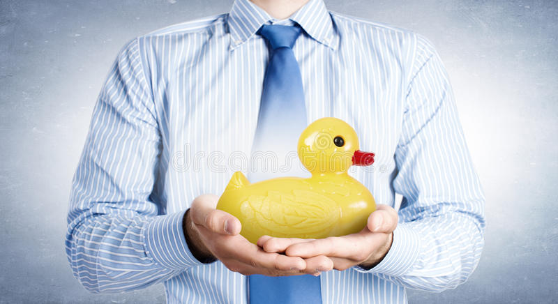 Decoy duck. Businessman holding in hands yellow toy rubber or plastic duck stock photography