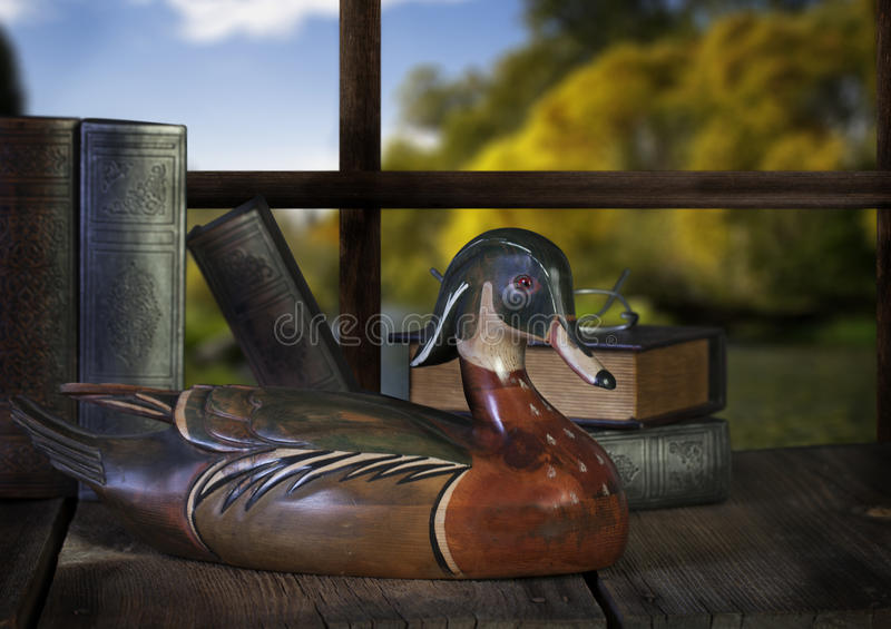 Decoy Wood Duck. A wood decoy duck on wood surface with old books and reading glasses in front of window. The view outside is of fall colored trees and river royalty free stock photography