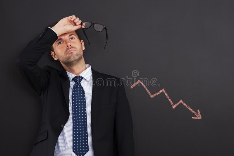 Decreased profit. Worried businessman with sign of decreased profit stock image