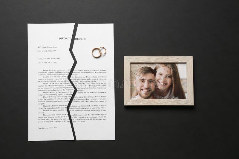 Decreto rasgado del divorcio, anillos y marco quebrado con la foto en fondo oscuro foto de archivo