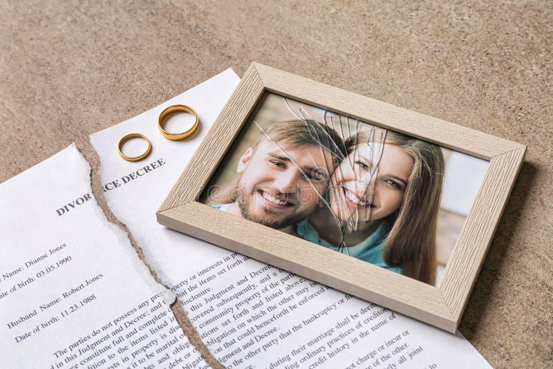 Decreto rasgado do divórcio, anéis e quadro quebrado com a foto na tabela imagens de stock