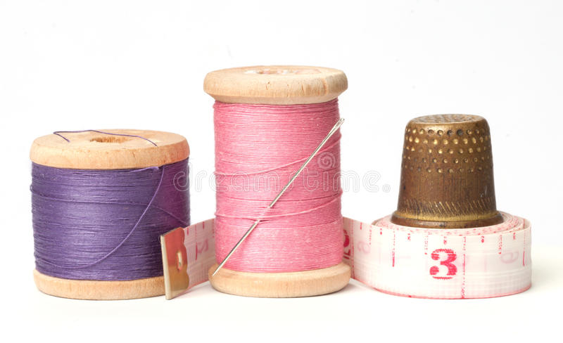Dedal e agulhas velhos com linha fotografia de stock