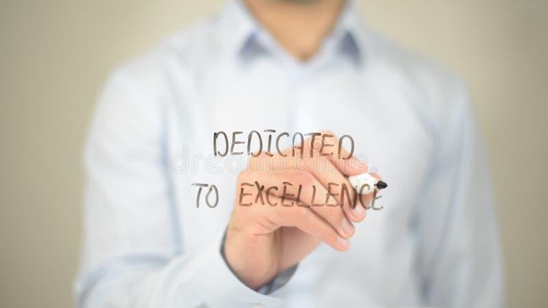 Dedicado à excelência, escrita do homem na tela transparente fotos de stock