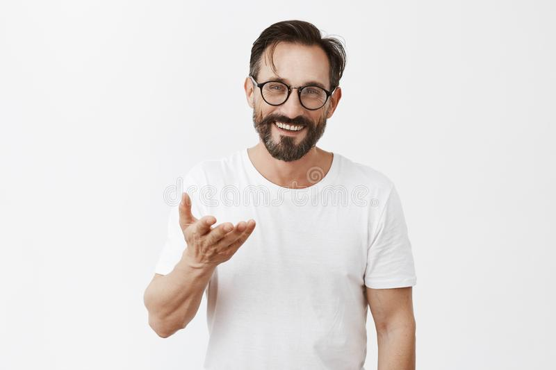 Dedicate everything to you. Charming grateful european male with beard and stylish haircut in glasses, pointing with. Palm at camera and smiling broadly, being stock photo