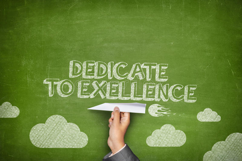 Dedicate to excellence concept. On green blackboard with businessman hand holding paper plane stock photos