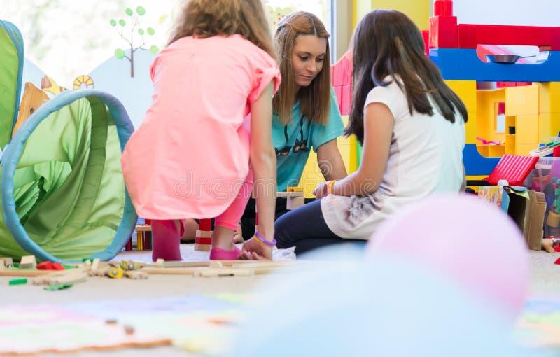 Dedicated kindergarten teacher coordinating a fun activity for t royalty free stock image