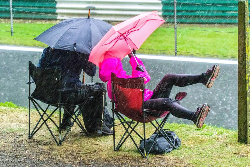 Dedicated Spectators. 22nd September 2019 - Cadwell Racetrack, Lincolnshire, England. Two spectators on camp chairs, with umbrellas, brave the downpour of rain royalty free stock photography