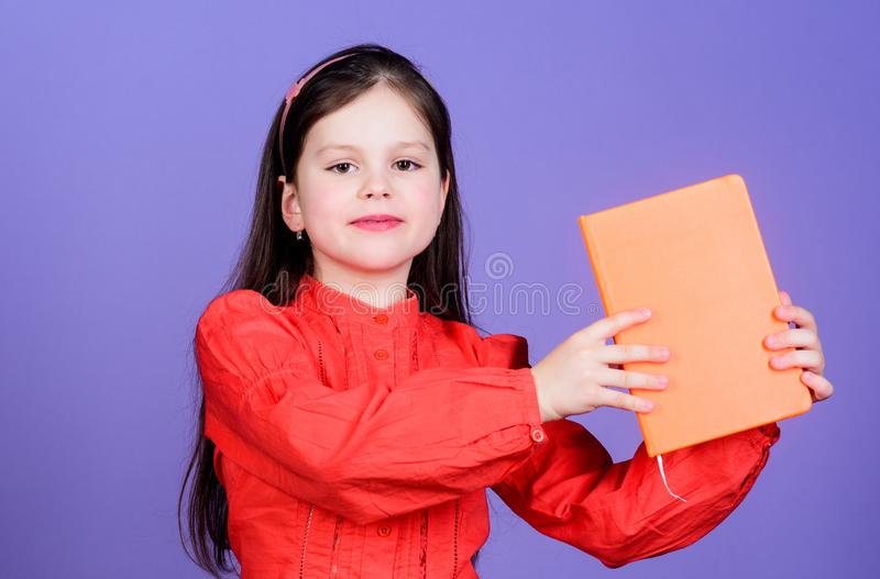 Dedicated to education. Little girl holding education book with orange cover. Cute small child getting formal education royalty free stock photo