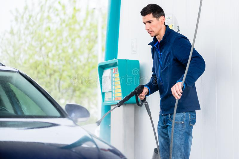Dedicated worker washing car with high-pressure hose. Dedicated young worker washing car manually with high-pressure hose royalty free stock photos