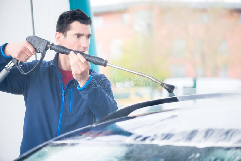 Dedicated worker washing car with high-pressure hose. Dedicated young worker washing car manually with high-pressure hose stock image
