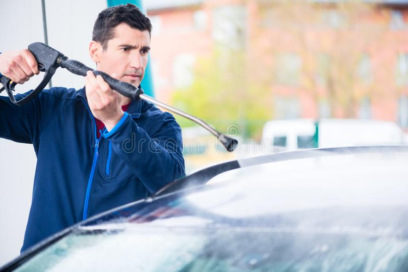 Dedicated worker washing car with high-pressure hose. Dedicated young worker washing car manually with high-pressure hose royalty free stock photo
