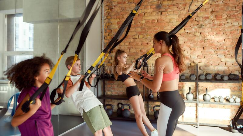 Dedication. Portrait Of Female Trainer Controlling, Looking After Kids While They Are Working Out With Fitness Straps In Stock Photo - Image of class, action: 184488706