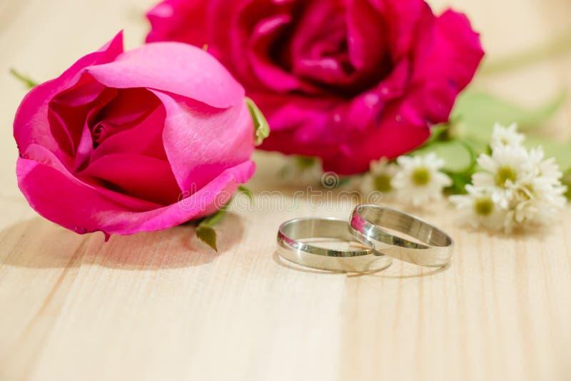 Dedique el anillo puesto cerca de rosas rojas en el fondo de madera imágenes de archivo libres de regalías