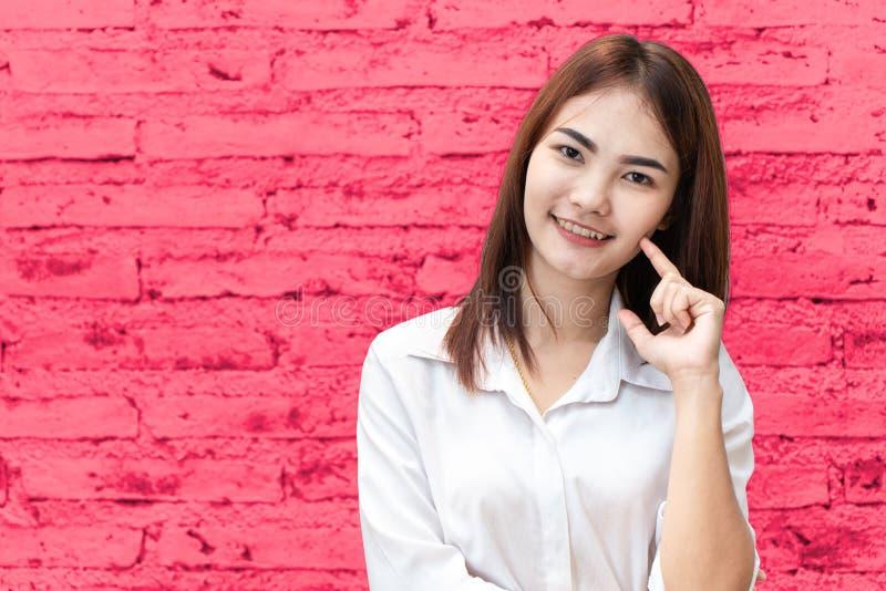 Dedo adolescente tailandês asiático bonito do sorriso da menina no fundo do rosa do mordente fotos de stock royalty free