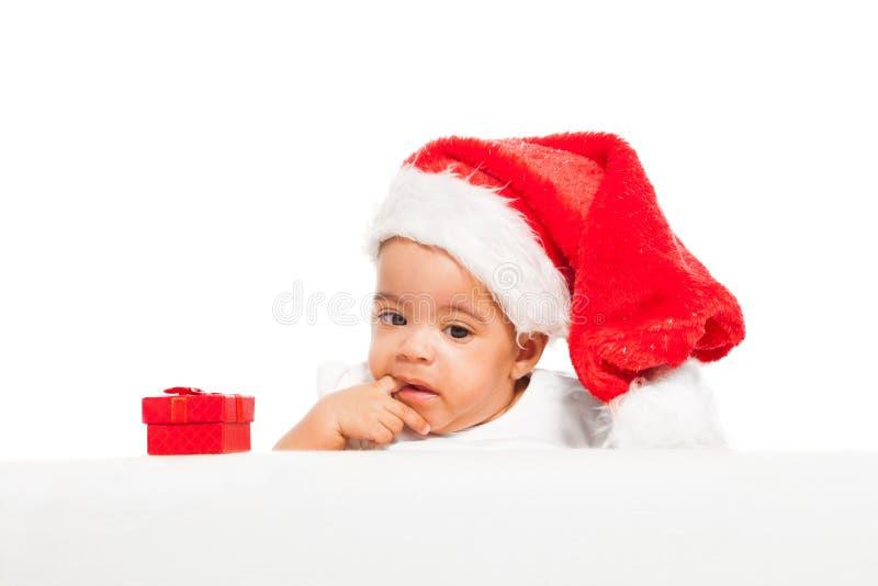 Dedo africano do paci do bebê que veste o chapéu vermelho do Natal fotografia de stock royalty free