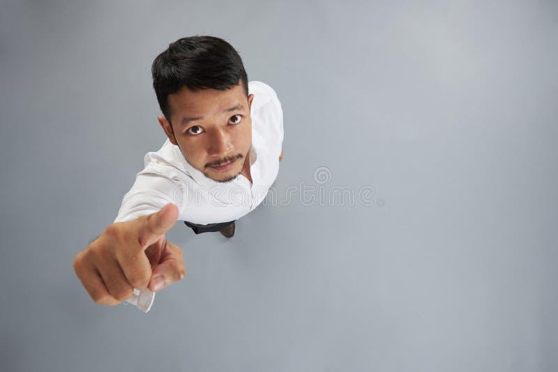 Dedo asiático do ponto do homem novo à câmera fotografia de stock royalty free