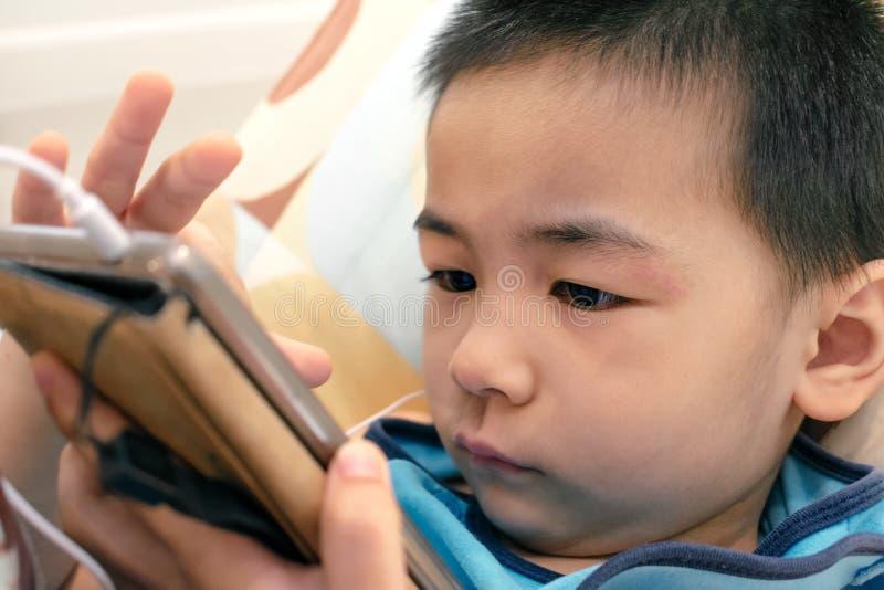 Dedo asiático dos furtos do menino através de um telefone esperto foto de stock royalty free